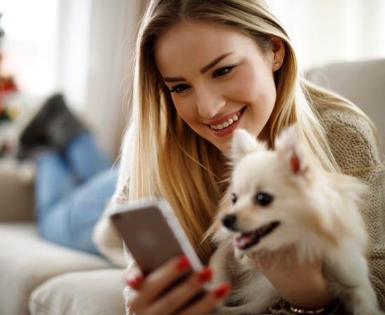 Download our App: Woman and Dog Looking at Phone